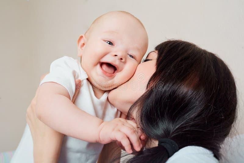 Großes Lächelnkleinkind Mamma, die Schätzchen umarmt Kind, das in den Armen von lacht stockfotografie