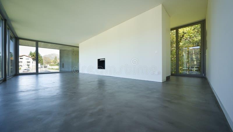 Großes leeres Wohnzimmer mit einem offenen Kamin und große Fenster lizenzfreie stockfotos
