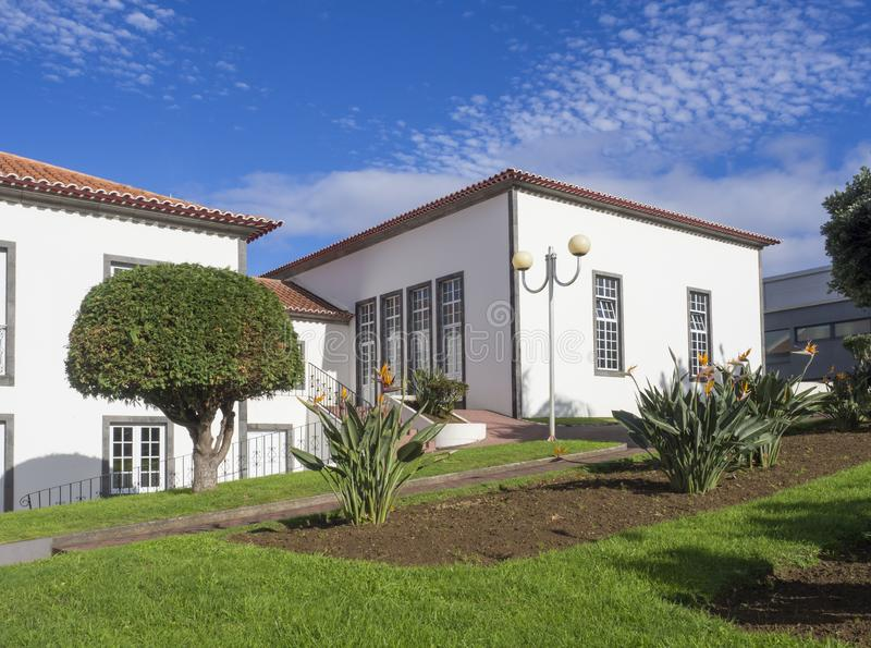 Großes neues weißes Landhaus an trditional Kolonialart von den Azoren, mit grünem Blumengarten und blauem Himmel an der Landschaf stockbild