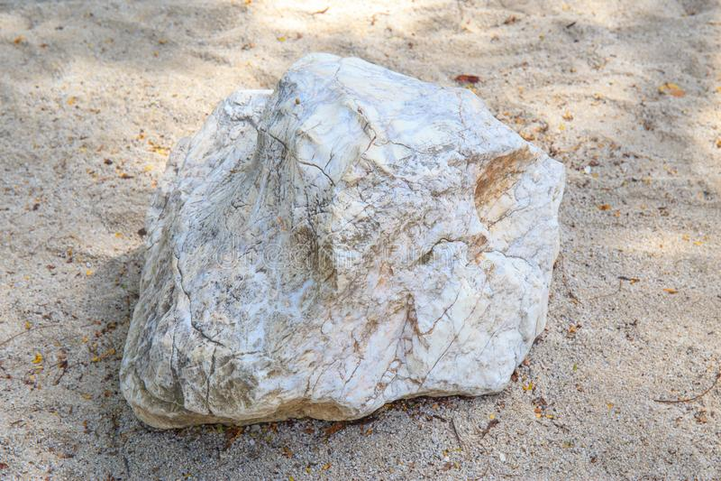 Großes oder großes schweres Stück des Marmorsteins oder des Felsens auf einem Sandboden mit Sonnenschein lizenzfreie stockbilder
