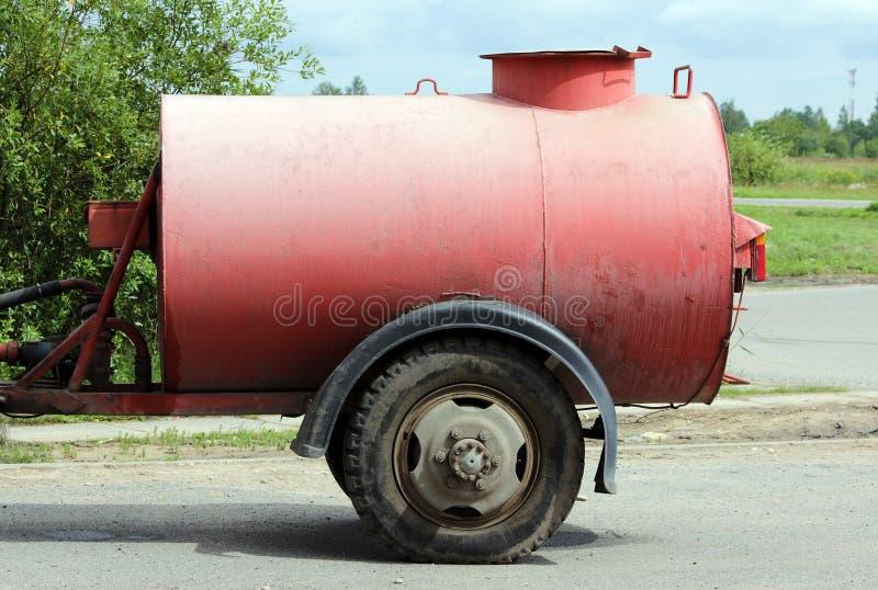 Großes rotes Bewässerungsfaß für die Straßen eingehangen zum Traktor in der Region Gatchina Leningrad stockfotografie
