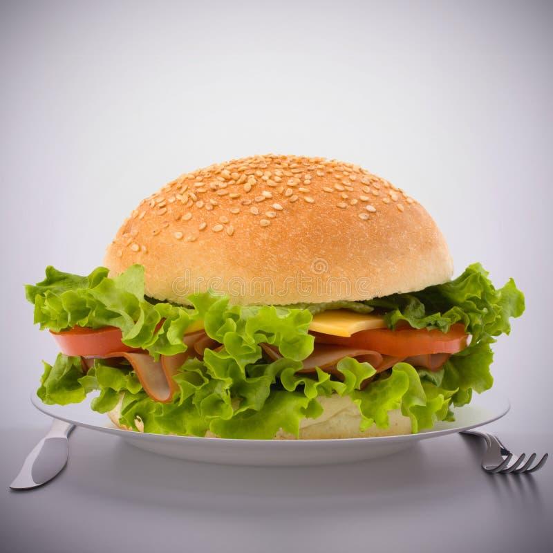 Großes Sandwich des Schnellimbisses auf Platte lizenzfreie stockfotografie