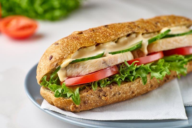 Großes Sandwich mit Huhn und Gemüse auf Teller lizenzfreies stockbild