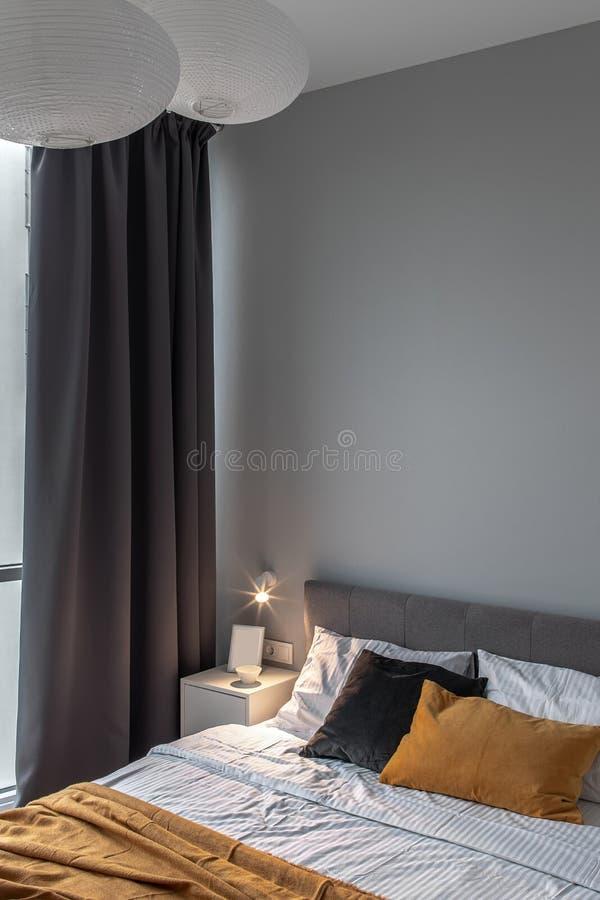 Großes Schlafzimmer in der modernen Art mit grauer Wand und leuchtender Lampe lizenzfreie stockbilder