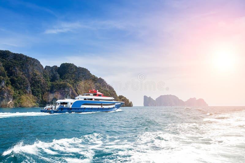 Großes Schnellbootblau Segeln auf dem Andaman-Meer an einem sonnigen Tag, der hinter einer Spur und Wellen auf dem Wasser verläss stockfotografie