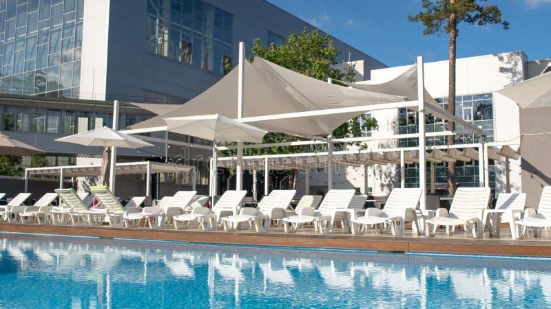 Großes Sommerpool mit sunbed und Sonnenschirme in einer LandErholungsstätte Konzept der Erholung und der Freizeit draußen stockbild