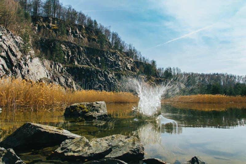 Großes Spritzen in überflutetem Steinbruch mit hohem trockenem Gras, kleiner Teich, Felsen, Tschechische Republik lizenzfreies stockfoto