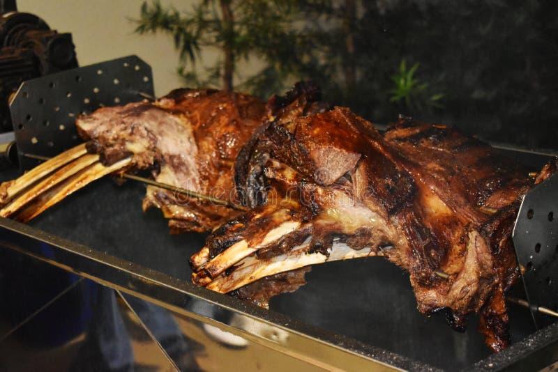 Großes Stück der Rindfleischrippe gebraten auf der Rolle Fleischgrill für viele Leute Gebratenes Rindfleisch Steak auf dem Knoche lizenzfreie stockbilder