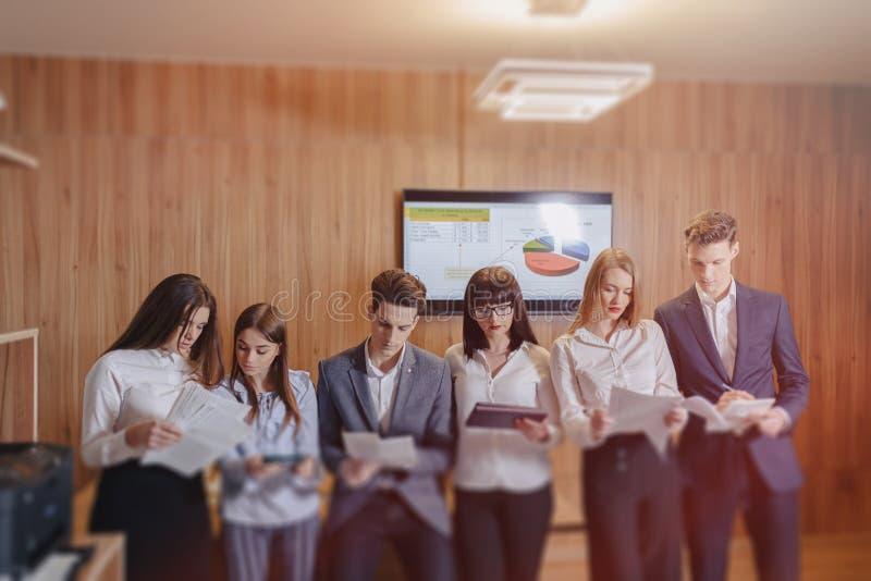 Großes Team von Leuten arbeitet bei einem Tisch für Laptops, Tabletten und Papiere, auf dem Hintergrund ein großer Fernseher a lizenzfreies stockbild