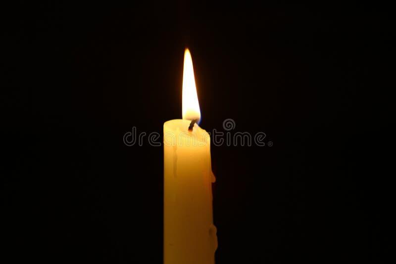 Großes Wachs, das gelbe Kerze mit großer Flamme auf dem dunklen Hintergrund beleuchtet lizenzfreies stockbild