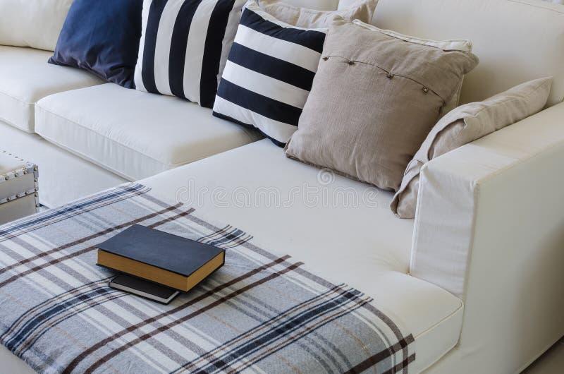 Großes weißes Sofa mit Kissen und Buch im Wohnzimmer lizenzfreie stockfotos