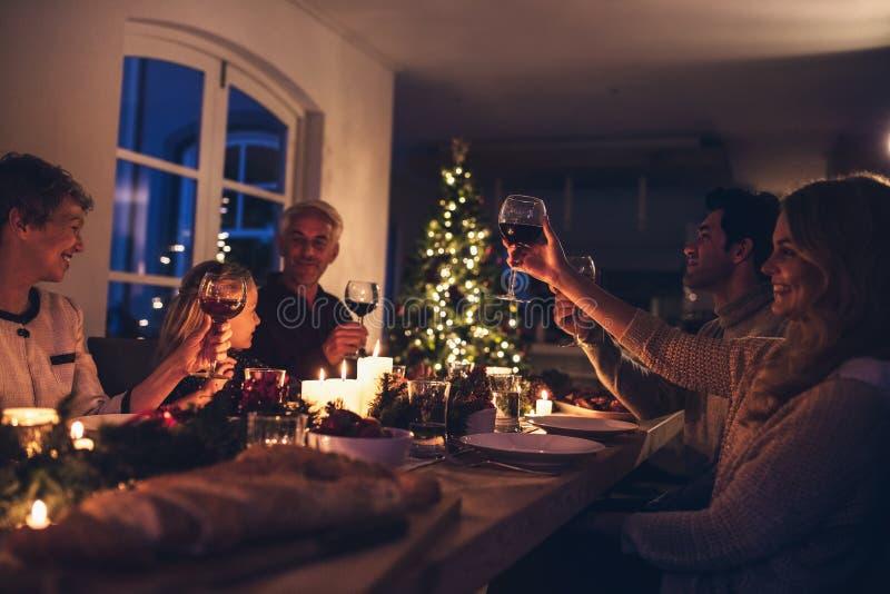 Großfamilie, die Wein am Weihnachtsabendessen röstet stockfotos