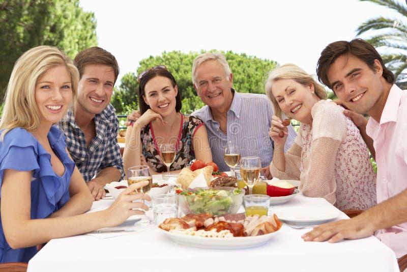 Großfamilie-Gruppe, die zusammen Mahlzeit im Freien genießt stockbild