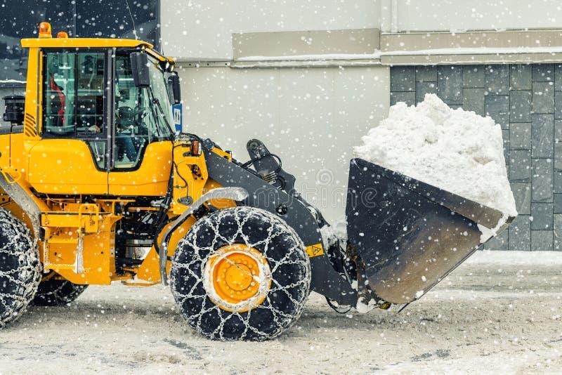 Großladermaschine mit Stahlketten, die im Winter im alpinen Gebirgsgebiet große Schneehöhe von der Stadtstraße entfernen schwer stockbild