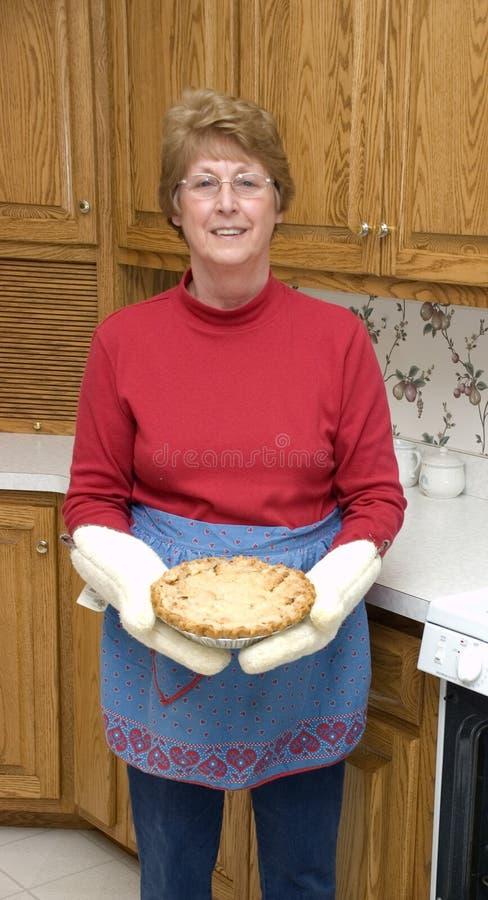 Großmutter-Backen-Apfelkuchen in ihrer Küche stockbild