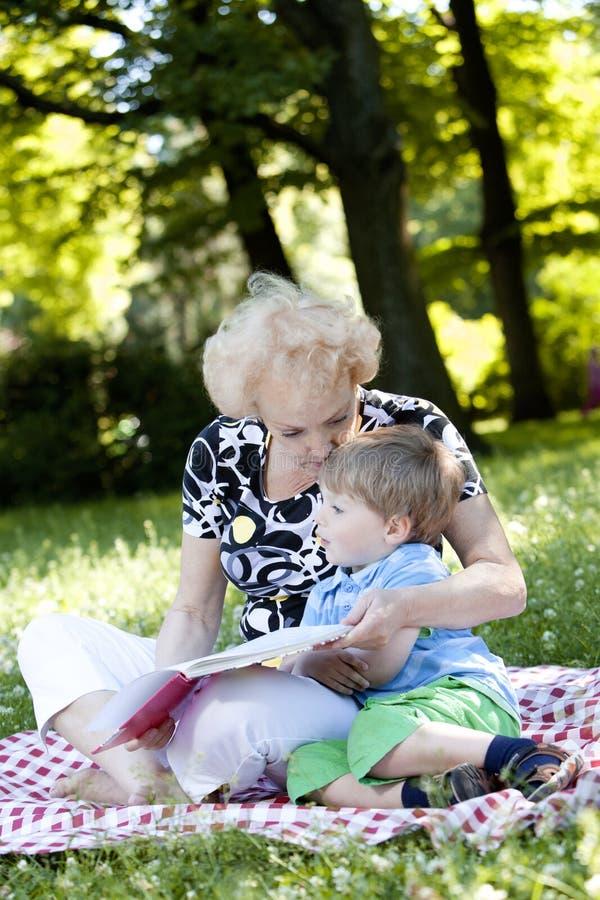 Großmutter, die das Buch zu ihrem Enkel liest lizenzfreie stockbilder
