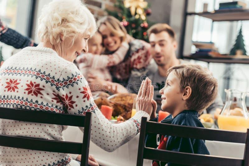 Großmutter, die dem Enkel Hoch fünf beim Feiern von Weihnachten mit unscharfer Familie gibt stockfotos