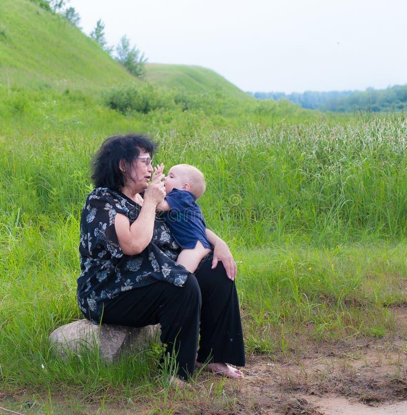 Großmutter, die draußen mit ihrem Enkel spielt stockbild
