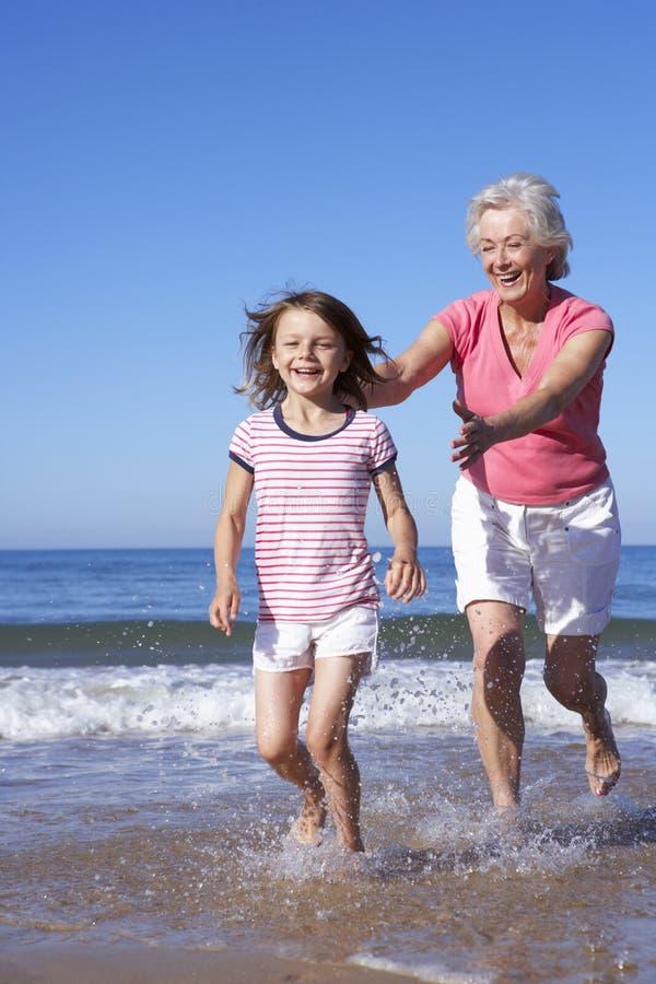 Großmutter, die Enkelin entlang Strand jagt stockfotos