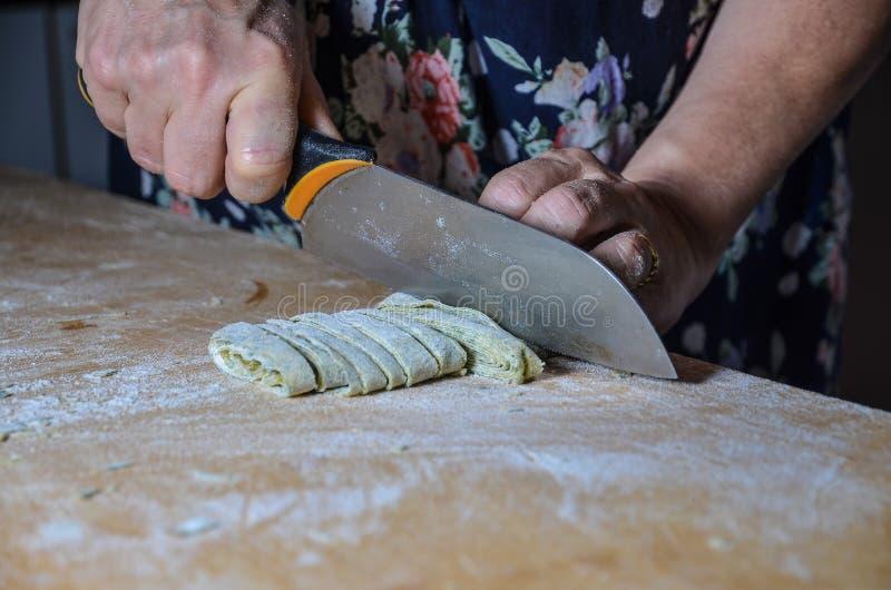 Großmutter, die frische Teigwaren mit Messer schneidet stockbild
