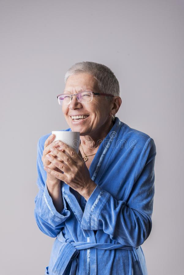 Großmutter, die Geruch des Kaffees genießt stockfotos