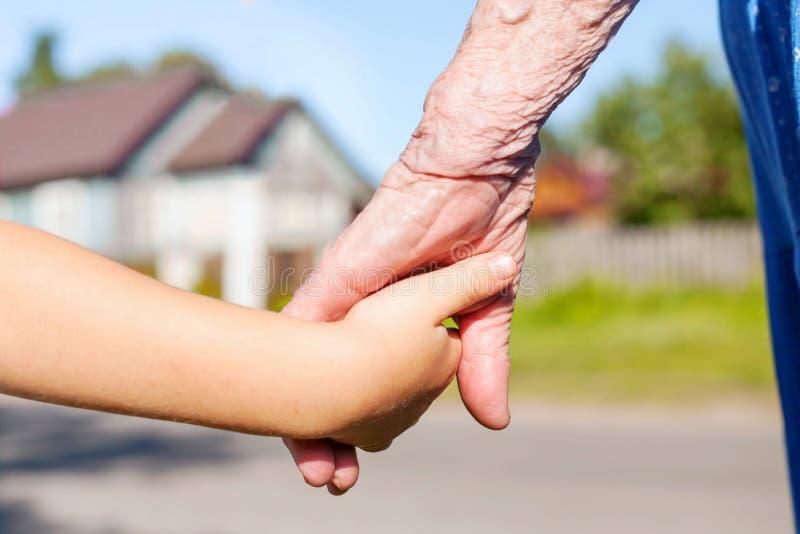 Großmutter, die Hand des jungen Enkelkindes nimmt lizenzfreie stockbilder