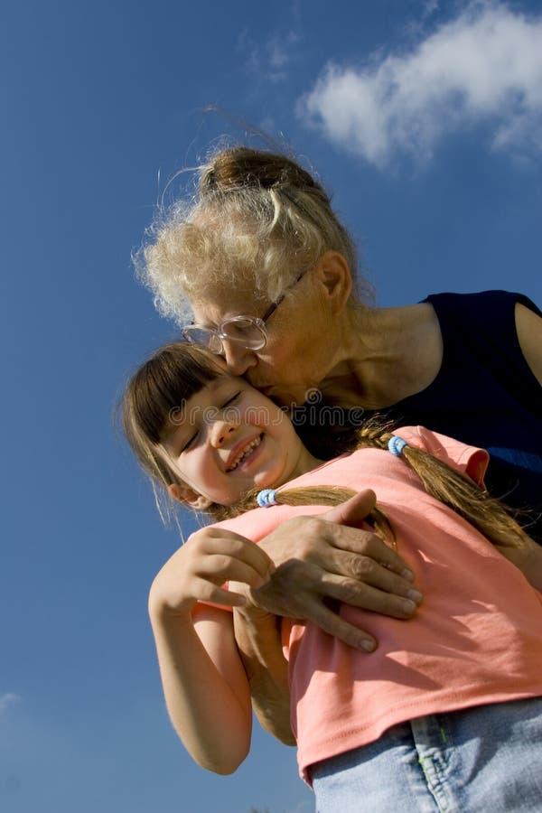 Großmutter, die ihre Enkelin küßt lizenzfreie stockbilder