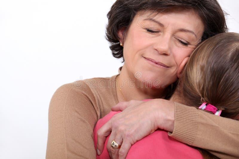 Großmutter, die ihre Enkelin umarmt lizenzfreies stockfoto