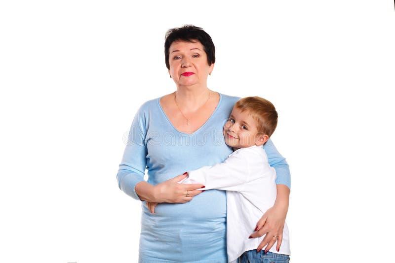 Großmutter, die ihren Enkel auf einem weißen Hintergrund umarmt stockfotos