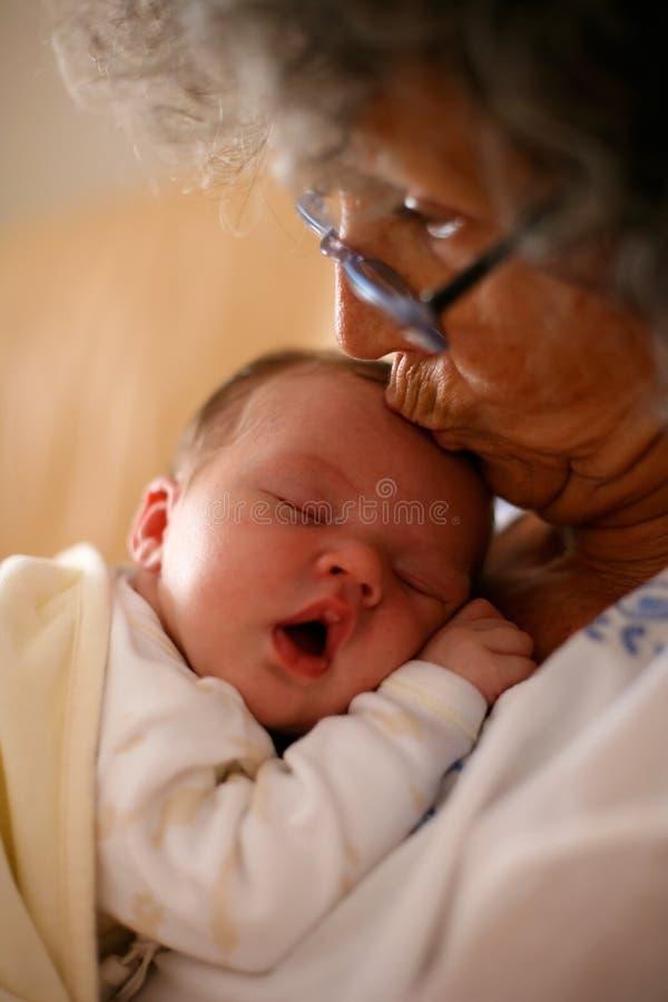 Großmutter, die Schätzchen küßt lizenzfreies stockbild