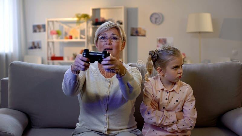 Großmutter, die Videospiel mit Steuerknüppel, beleidigte Enkelin vorbei sitzt spielt lizenzfreie stockbilder