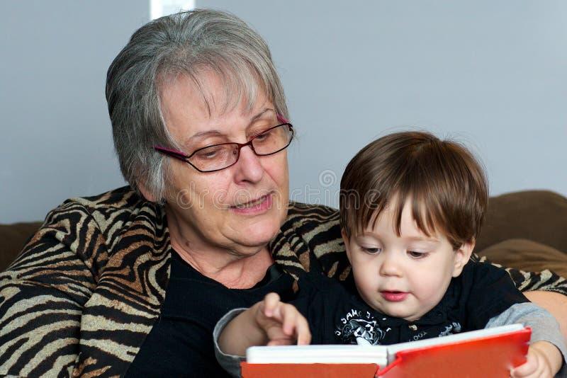 Großmutter, die zum Enkelkind liest stockbild