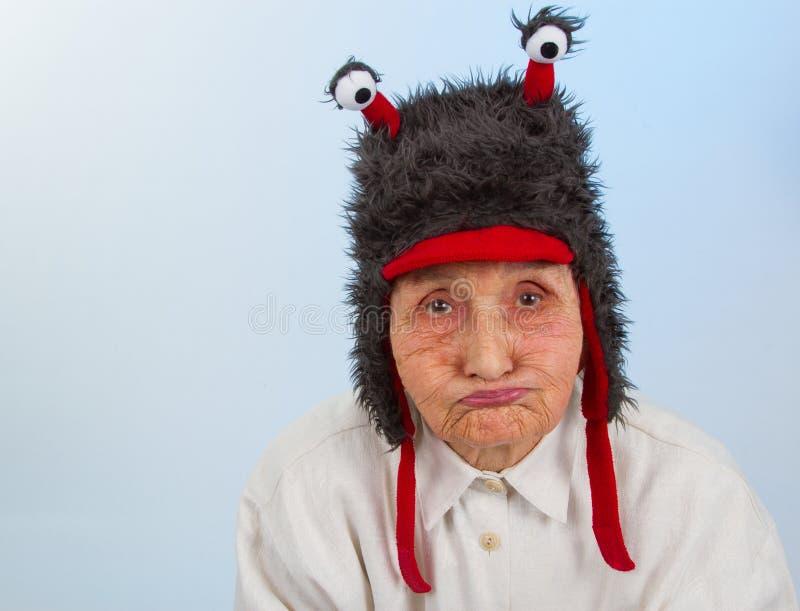 Großmutter im lustigen Hut mit einem mürrischen Ausdruck stockbild