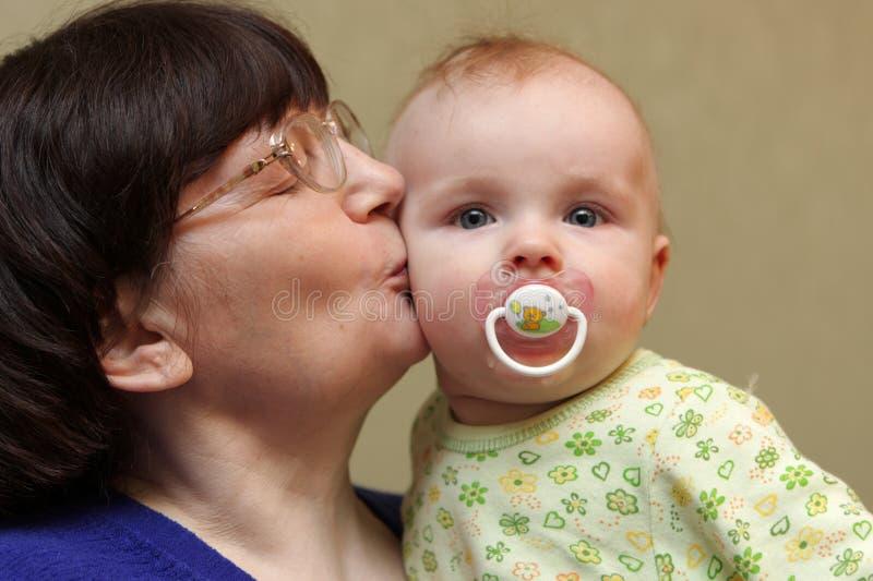 Großmutter küßt Schätzchen lizenzfreies stockfoto