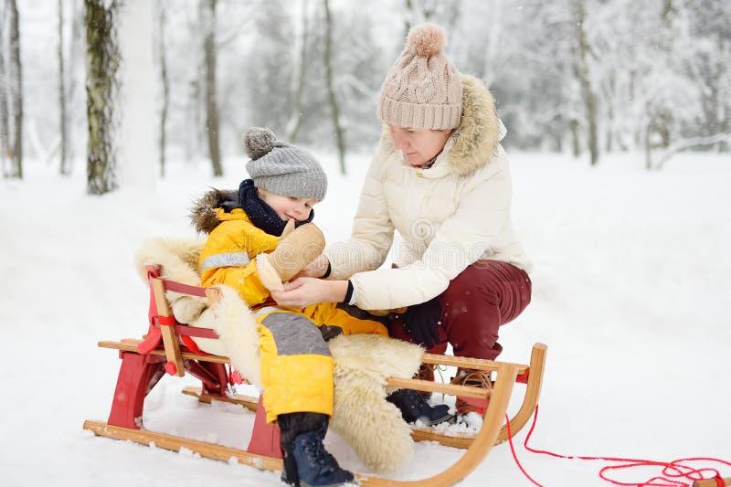 Großmutter/Kindermädchen/Mutter legt an einen Handschuh einem kleinen Kind während des Rodelns in Winterpark vor stockbilder