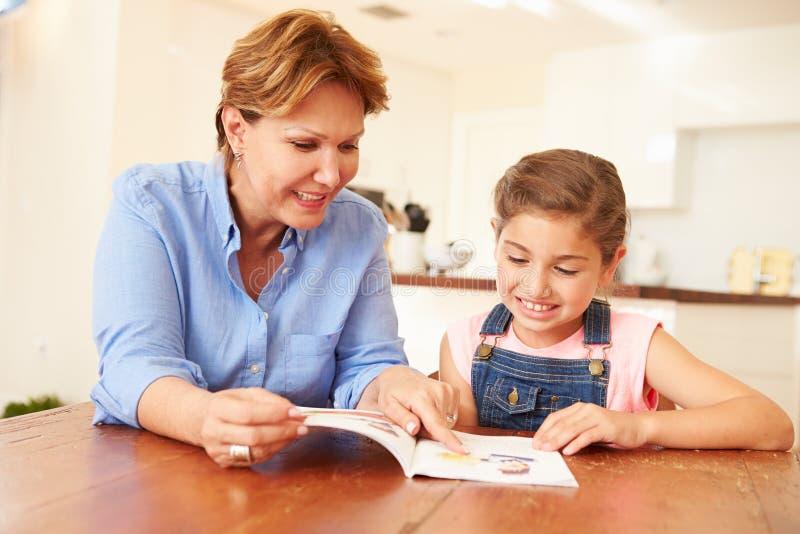 Großmutter-Lesung mit Enkelin zu Hause stockfotografie