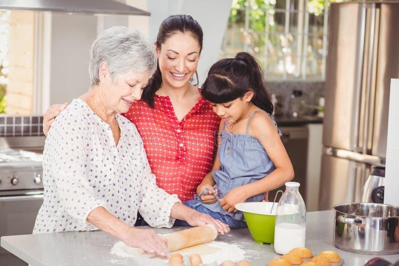 Großmutter mit der Familie, die Brot macht stockfotos