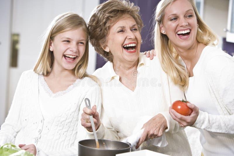 Großmutter mit der Familie, die in der Küche lacht lizenzfreie stockbilder
