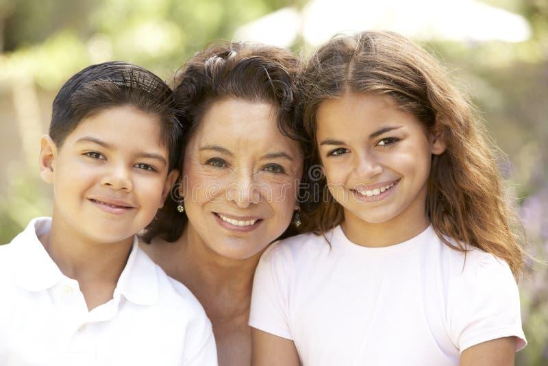 Großmutter mit Enkelkindern im Garten lizenzfreies stockfoto