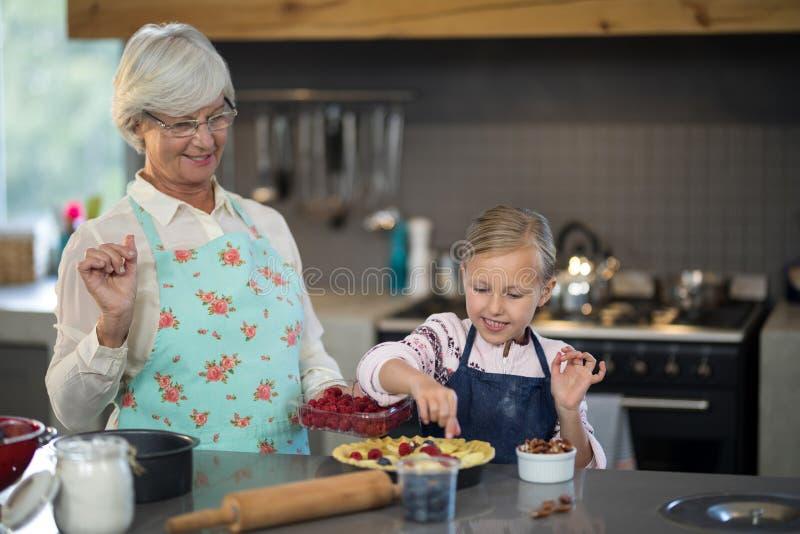 Großmutter und Enkelin, die Erdbeeren der Kruste hinzufügen stockbild