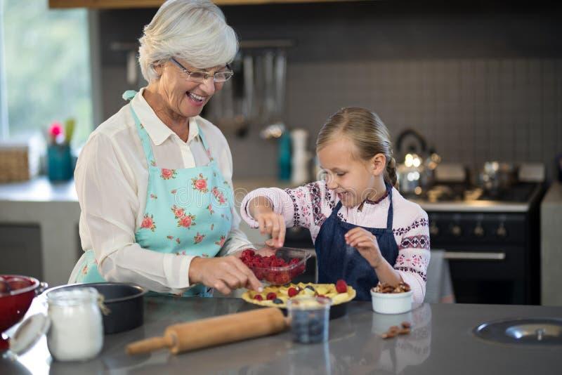 Großmutter und Enkelin, die Erdbeeren der Kruste hinzufügen lizenzfreie stockfotografie