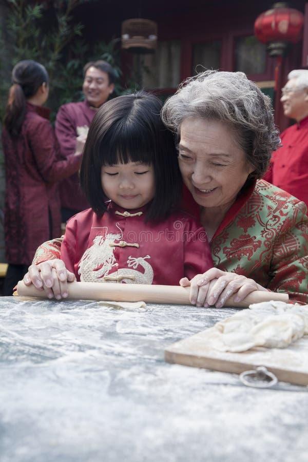 Großmutter und Enkelin, die Mehlklöße in der traditionellen Kleidung machen stockbilder