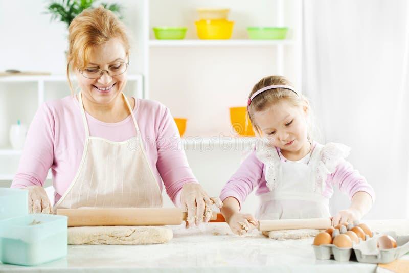 Großmutter und Enkelin, die Teig machen lizenzfreies stockfoto