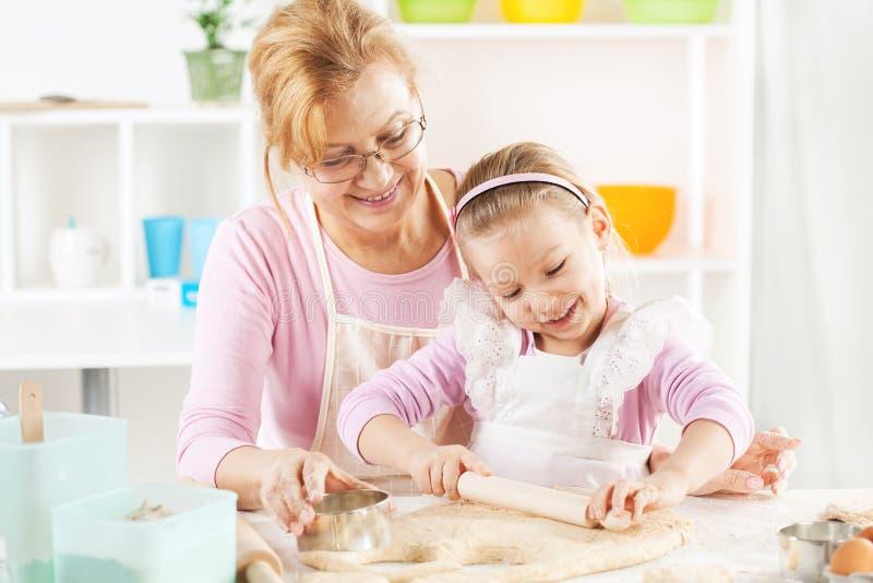 Großmutter und Enkelin, die Teig machen lizenzfreie stockbilder