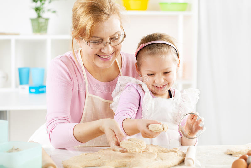 Großmutter und Enkelin, die Teig machen lizenzfreies stockbild