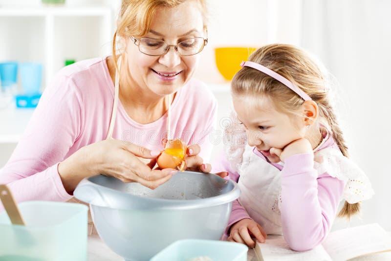 Großmutter und Enkelin in einer Küche stockbild