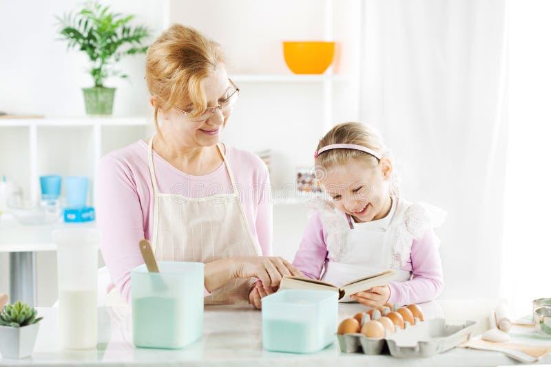 Großmutter und Enkelin in einer Küche. stockfotografie