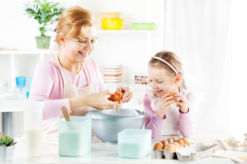 Großmutter und Enkelin in einer Küche stockfotos