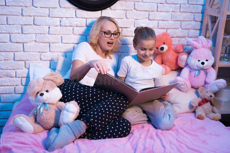 Großmutter und Enkelin lesen lange Buch nachts zu Hause lizenzfreie stockbilder