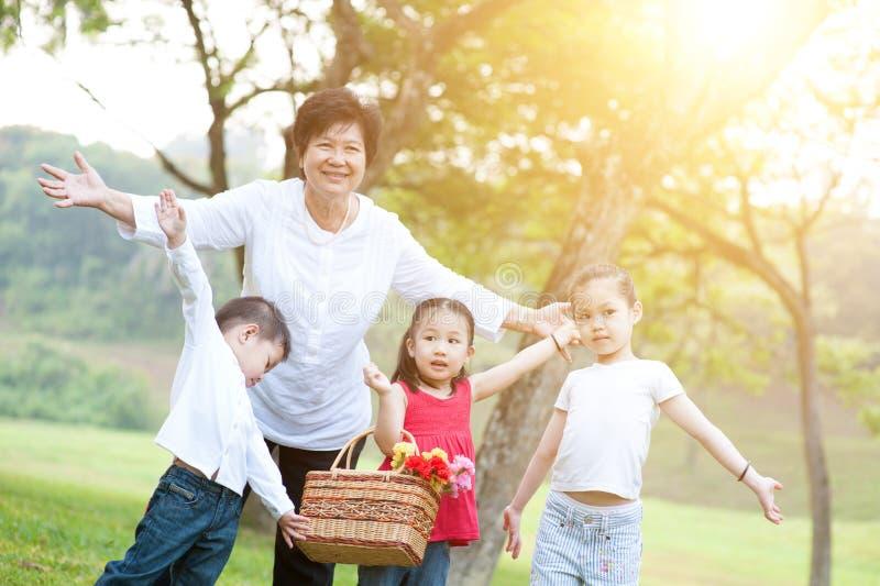 Großmutter und Enkelkinder, die Spaß an im Freien haben stockfotografie